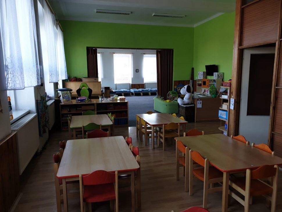 Průhled celou třídou II. - ze začátku jsou jídelní stoly, dále navazuje hrací koutek av pozadí jdou vidět postýlky naspaní