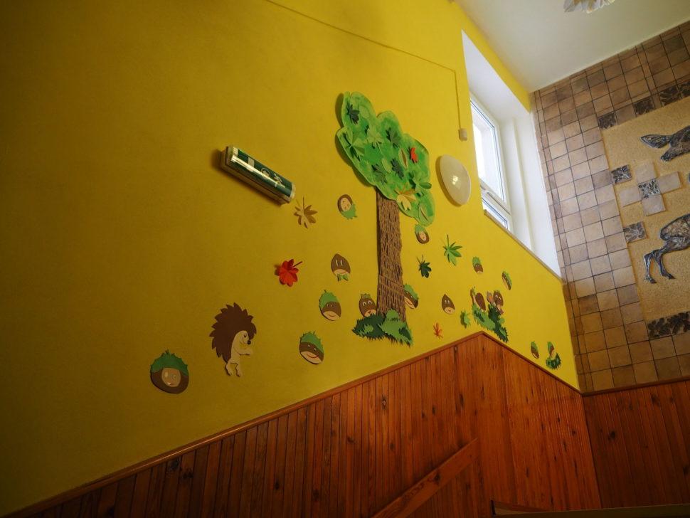 Schody doprvního patra - nastěně je umístěn strom apod ním obrázky kaštanů.